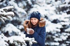 Vinterstående av den förtjusande lyckliga barnflickan i varm kläder som spelar med snö royaltyfria bilder