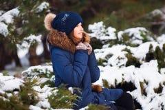 Vinterstående av den förtjusande lyckliga barnflickan i varm kläder som spelar med snö fotografering för bildbyråer