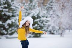 Vinterstående av den härliga le kvinnan med snöflingor i vita pälsar royaltyfri foto