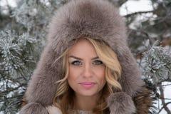 Vinterstående av den härliga le kvinnan med snöflingor i vita pälsar Arkivfoto