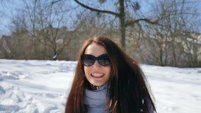 Vinterstående av den härliga vuxna flickan i mörk solglasögon som tycker om solig dag och väntar på en vår som spenderar tid stock video