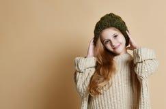 Vinterstående av den lyckliga lilla flickan som bär den stack hatten och tröjan arkivfoton