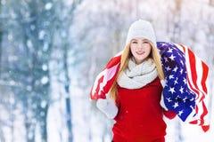 Vinterstående av den unga tonåriga flickan med USA flaggan Parkerar den glade modellen Girl som för skönhet skrattar och har gyck Arkivfoton