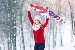 Vinterstående av den unga tonåriga flickan med USA flaggan Parkerar den glade modellen Girl som för skönhet skrattar och har gyck Arkivfoto