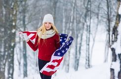 Vinterstående av den unga tonåriga flickan med USA flaggan Parkerar den glade modellen Girl som för skönhet skrattar och har gyck Royaltyfri Fotografi