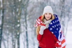 Vinterstående av den unga tonåriga flickan med USA flaggan Parkerar den glade modellen Girl som för skönhet skrattar och har gyck Royaltyfria Bilder