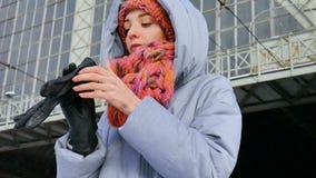 Vinterstående av en ung kvinna i blått lag och färgrik hatt på järnvägsstationen under solig kall dag lager videofilmer