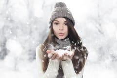 Vinterstående. Barn härlig kvinna som blåser snow Fotografering för Bildbyråer