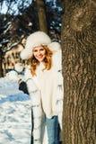 Vinterståenden av den lyckliga kvinnan med kastar snöboll utomhus- royaltyfri foto