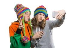 Vinterståenden av två lyckliga härliga tonårs- flickvänner i stack hattar som har gyckel med mobiltelefonen som tar selfie, isole arkivfoton
