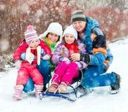 Vinterstående av den lyckliga unga familjen Arkivfoto