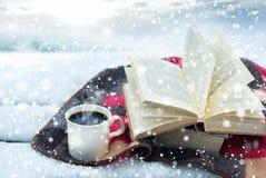 Vinterstilleben: kopp kaffe och öppnad bok Arkivfoto