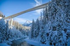 Vinterunderland med floden och stakbåten d' En Vulpera i Schweiz fotografering för bildbyråer