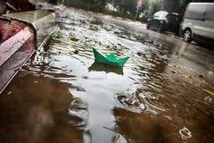Vinterväder i Israel Det pappers- fartyget seglar i en pöl under regnet arkivbilder