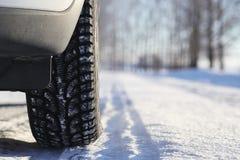 Vinterväg och en bil arkivfoton