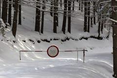 Vintervägen längs skogen med teckentillträdeet förbjudas hangin Arkivfoto