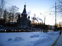 Vintervägen som kör till och med staden, aftonljusen, är ljus, bilar som reser på huvudvägen med ljusen på, kyrkan fotografering för bildbyråer