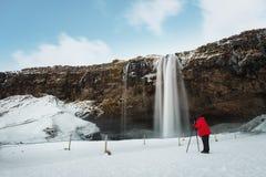 Vintervattenfalllandskap, fotograf i det röda omslaget som tar fotografiet med kamerastativet på den Seljalandsfoss vattenfallet  royaltyfri foto