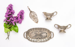 Vintgae silver dishes and lilac flowers. Flat lay Stock Photos