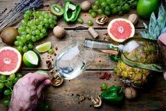 Vintillverkare som h?ller ungt vitt bio vin f?r att smaka med druvor, muttrar och frukt p? den gamla tr?tabellen arkivbilder