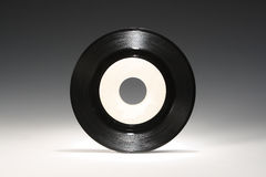 Vinyl 45 RPM Record. White blank white label on graduated gray background Royalty Free Stock Photos
