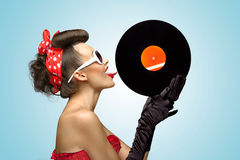 The vinyl desire. A photo of glamorous pin-up girl touching vinyl LP with tongue Stock Photos