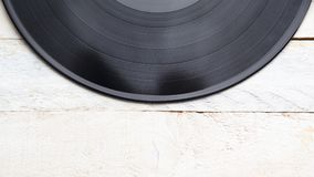 Vinyl disc background on a white wooden table, top view. Empty copy space for Editor`s text royalty free stock image