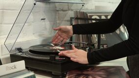 The Vinyl Player. Vinyl disc on the player, woman hands reversing side stock video footage
