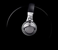 Vinyl DJ. A pair of DJ style headphones wrapped around a record isolated on black Royalty Free Stock Photography