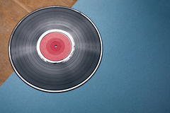 Vinyl musical disc on blue and wooden background; Royalty Free Stock Image