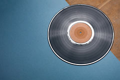 Vinyl musical disc on blue and wooden background; Royalty Free Stock Photos