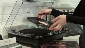 The vinyl player. Vinyl disc on the player, woman hands reversing side stock footage