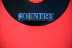 Vinyl record with country word in metal type with copy space Royalty Free Stock Photo