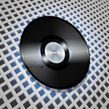 Vinyl record with metallic centre on lattice pattern background Royalty Free Stock Photography