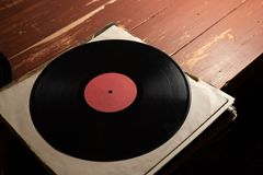Vinyl record on old red wooden background. Copy space for your label stock photos
