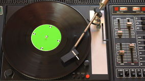Vinyl record pleer. Plays song from an old turntable 4k top view. Black background. Music round plate rotate. Music disc turn. Tracking shot rotating disk with stock video footage