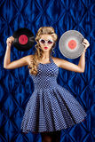 Vinyl record. Pretty pin-up woman with retro hairstyle and make-up posing with vinyl record over vintage background Royalty Free Stock Photo