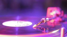 Vinyl record rotating on sound deck, light flashing in nightclub. Stock footage stock video