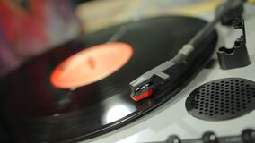 Vinyl record spinning on retro music player at vintage musical instruments store