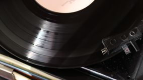 Vinyl record spins on the player. The needle head of the player moves along the track. Everything is covered with dust. View from above stock video footage