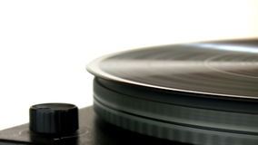 Vinyl record on turntable. Close up of vinyl record spinning on turntable isolated on white. Turntable spins and stops stock video footage