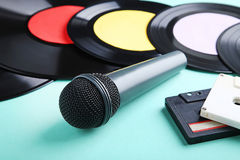 Vinyl records with cassette tapes. And microphone on mint background stock images