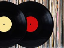 Vinyl records in front of pile of many close standing vinyl disks in old color covers over black background. Black records with color labels in front of pile of Stock Images