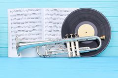 Vinyl records, trumpet and musical notes. Vinyl disc, rusty trumpet and musical papers on blue wood. Vintage musical equipment royalty free stock photos