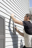 Vinyl Siding - DIY Repairs. A homeowner works on a DIY project to repair exterior vinyl siding stock photo