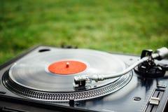 Vinyldiskett som spelar på skivtallriken, bakgrund för grönt gräs arkivfoto