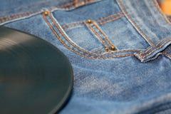 Vinyldiskette auf Jeans Stockbild