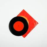 vinylrekord för 45 r/min. och gammalt ridit ut kuvert på vit Royaltyfri Foto