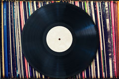Vinylrekord med kopieringsutrymme framme av en samling av album, tappningprocess Royaltyfri Fotografi