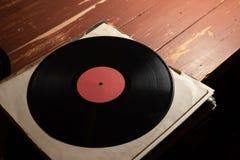 Vinylrekord på gammal röd träbakgrund Kopieringsutrymme för din etikett arkivfoton